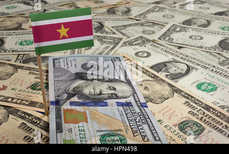Flag of Suriname sticking in a variety of american banknotes.(series) - Stock Photo