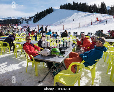 Family and friends skiers on a winter holiday enjoying sunshine dining outside a ski restaurant in French Alps. - Stock Photo