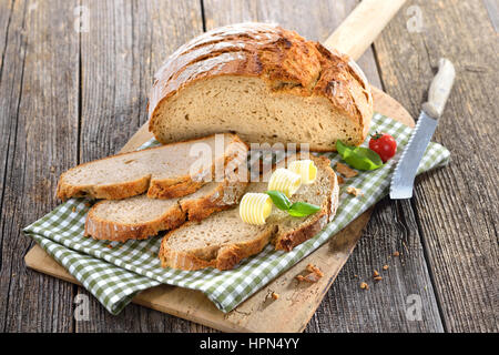 Fresh stone oven baked bread with butter rolls served on an old wooden baking board - Stock Photo