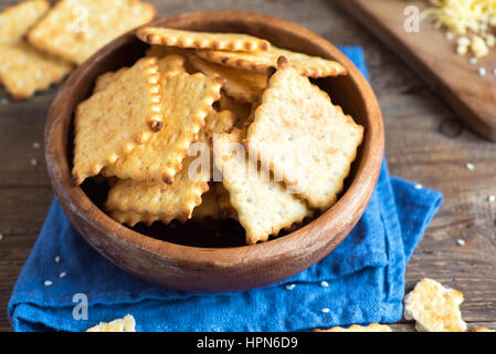 Homemade thin crispy cheesy crackers with sesame seeds in rustic wooden bowl - fresh organic homemade baking cheese - Stock Photo