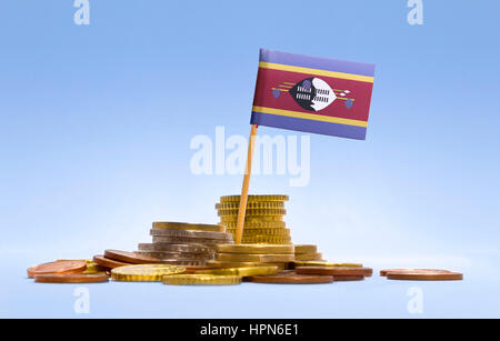 Flag of Swaziland in a mixed stack of european coins and a blue background.(series) - Stock Photo
