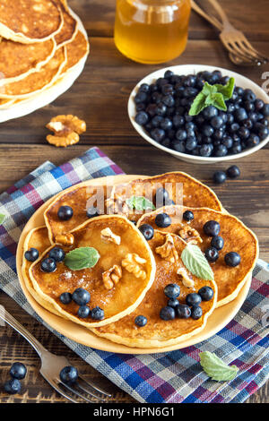 Pancakes on plate with blueberries, walnuts and honey for healthy breakfast - homemade healthy vegetarian food - Stock Photo