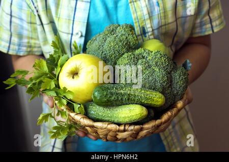 Person (hands) hold basket with organic green vegetables (broccoli, cucumbers, apple and parsley) - healthy organic - Stock Photo