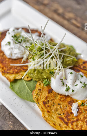 Brunch Idea; Pancakes with guacamole, spinach and poached eggs. Garnished with parsley, pumpkin seeds and pepper - Stock Photo