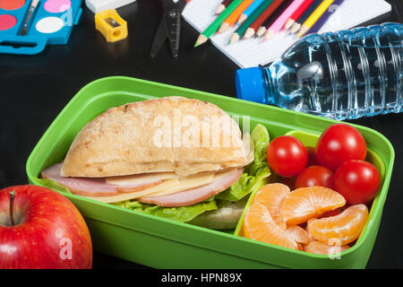 School lunch. Sandwich, small tomatoes, tangerine, apple in plastic lunch box and bottle of water on black chalkboard. - Stock Photo
