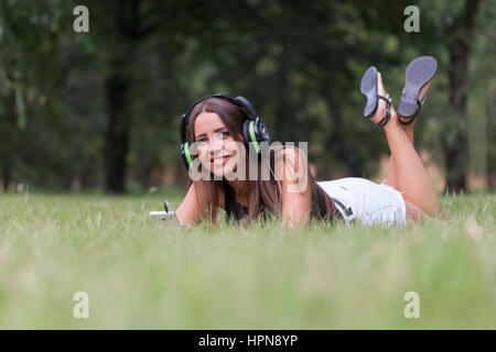 Beautiful young woman listening to music in nature, Selective focus and small depth of field, lens flare - Stock Photo