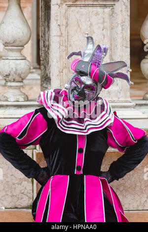 A woman is seen outside the Doge's Palace wearing a traditional Volto mask during the 2017 Venice Carnival - Stock Photo