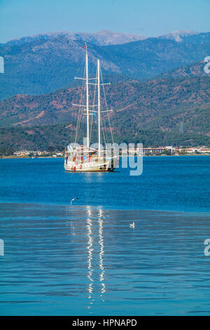 Boat anchored in a tranquil bay, sakin koyda demirlemis mavi tur teknesi, akdeniz turkiye mavi tur, turkey yacht - Stock Photo