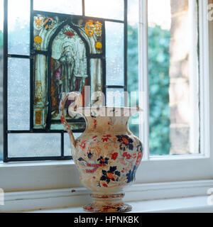 A vase on a windowsill with stained glass. - Stock Photo