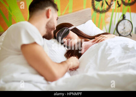 Man wakes up his girl with sleeping mask in the morning - Stock Photo