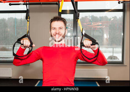 Crossfit instructor at the gym doing Excersise. Fitness man workout on the rings. Fitness man in the gym. Fitness - Stock Photo
