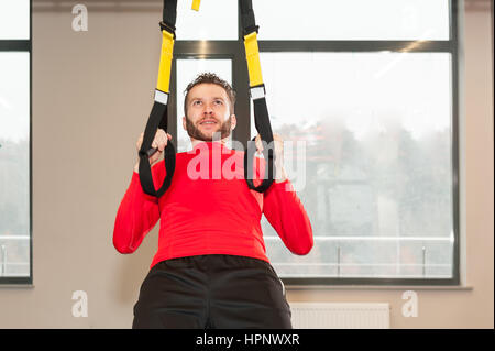 Sporty male exercising do y deltoid fly with fitness trx straps in gym - Stock Photo