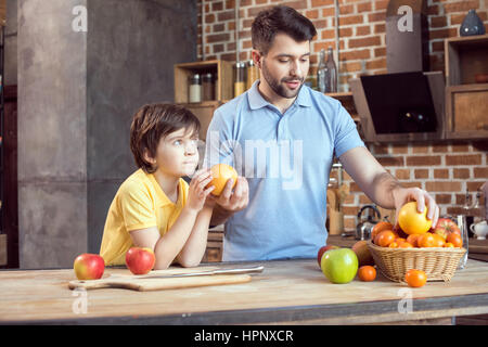 Father and son selecting fruits from basket - Stock Photo