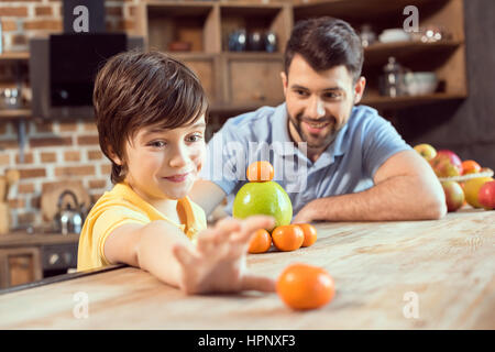 father and son playing with citrus fruits in kitchen - Stock Photo