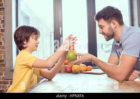 happy father and son playing with citrus fruits in kitchen - Stock Photo