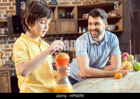 father looking at little son squeezing fresh juice in kitchen - Stock Photo