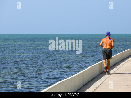 Key West, USA - May 10, 2015: Man running along the blue sea in blazing sun on the Florida Keys Overseas Heritage - Stock Photo