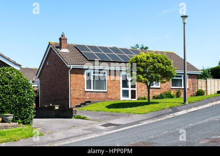 Solar panels on the roof of a small bungalow on a summer day with bright blue sky. - Stock Photo