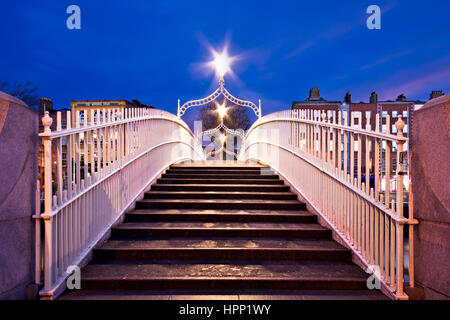 Night Time symmetrical view of the steps leading on to the Ha'penny Bridge in Dublin Ireland.Three lanterns light - Stock Photo