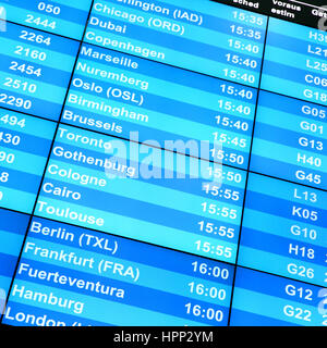 Modern flight information board in an airport close-up - Stock Photo