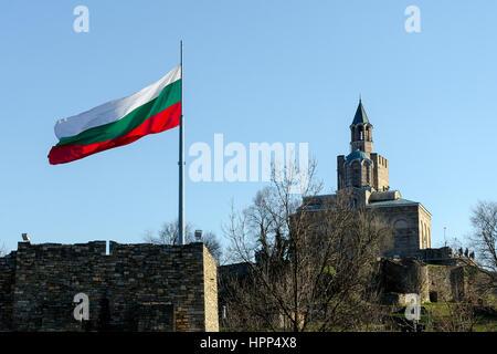 Waving Bulgarian flag at Tsarevets fortress with patriarch church in background, Veliko Tarnovo, Bulgaria - Stock Photo
