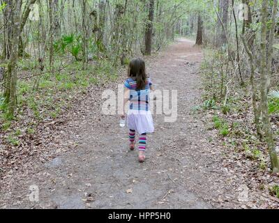 Young girl with water bottle hiking through the woods, Gainesville, Florida, USA - Stock Photo