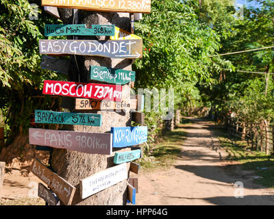 Signpost with wooden signs in many colors - Stock Photo