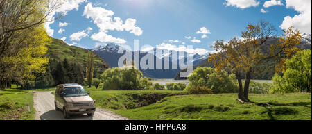 Car on road, Matukituki Valley, snowy Mount Aspiring, Mount Aspiring National Park, Otago, Southland, New Zealand - Stock Photo