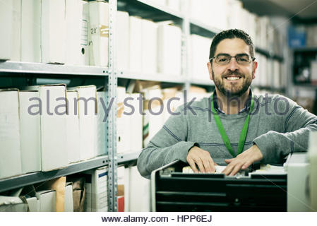 Portrait of man searching for files in an archive - Stock Photo