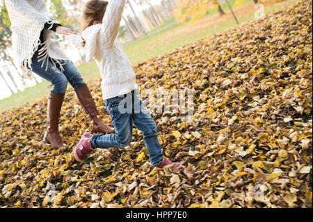 Girl running with mother in autumnal leaves - Stock Photo