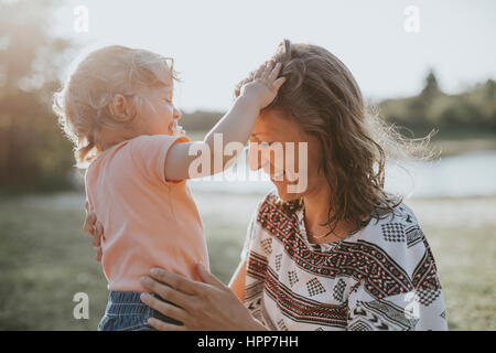 Mother and little daughter relaxing in nature - Stock Photo