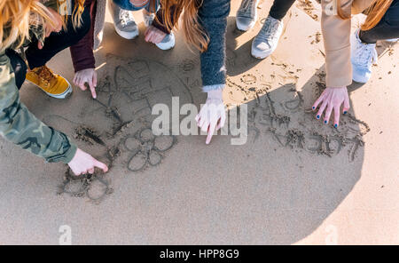 Four friends drawing in the wet sand on the beach, partial view - Stock Photo