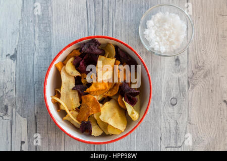 Vegetable chips and pyramide salt in bowls - Stock Photo