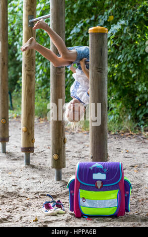 Smiling little girl with school bag on high bar of a playground - Stock Photo