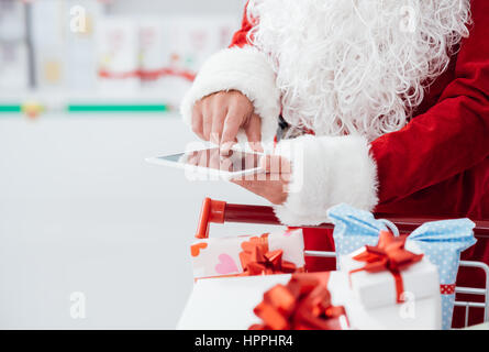 Santa Claus doing Christmas shopping at the supermarket, he is using apps on a digital tablet and pushing a cart - Stock Photo