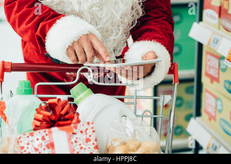 Santa Claus using a touch screen tablet at the supermarket and doing grocery shopping, he is pushing a full cart, - Stock Photo