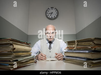 Angry office worker with piles of folders in a small room. - Stock Photo