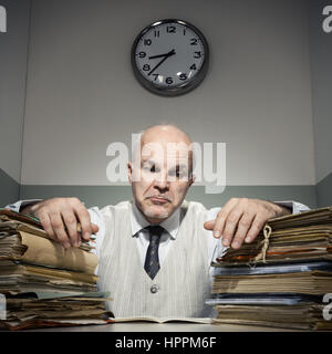 Overworked sad businessman with piles of folders. - Stock Photo
