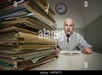Stressed office worker with a pile of folders in his small room. - Stock Photo