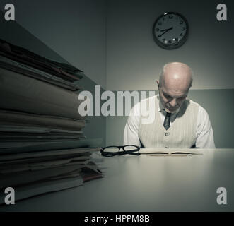 Tired sad clerk reading documents in his small office. - Stock Photo