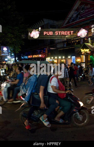 Busy street scene in Siem Reap, Cambodia, looking down 'Pub Street' with mopeds, locals, tourists and tuk tuks. - Stock Photo