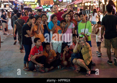 A group family of Asian tourists on Pub Street, Siem Reap, taking a self portrait with a selfie stick and mobile phone on a busy night street scene. Stock Photo