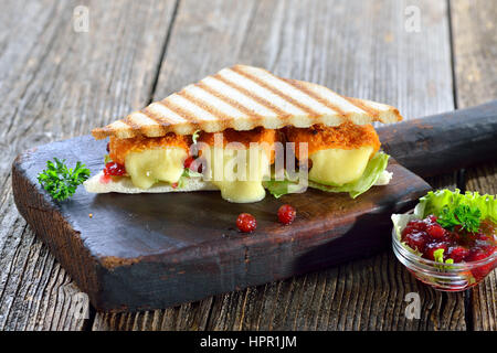 Toasted panini triangles with breaded mini camembert cheese loaves, cranberries and iceberg lettuce served on a - Stock Photo