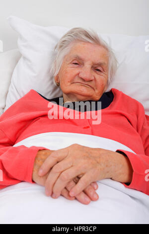 Portrait of a beautiful elderly lady in her bed - Stock Photo