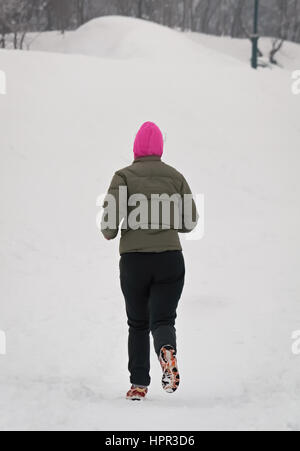 Young girl running in a cold and snowy winter day - Stock Photo