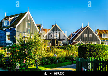 Typical traditional houses with green wall and red tiled roof in the historic fishing village of Marken in the Netherlands - Stock Photo