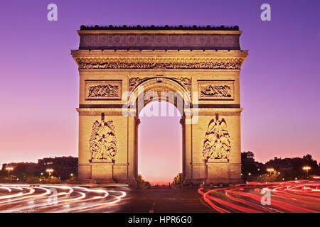 A dawn view of the Arc de Triomphe taken from the Avenue de la Grande Armee. The light trails of traffic lead to - Stock Photo