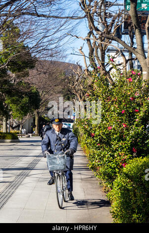 A security guard riding on a bicycle on the pavement outside the Tokyo Imperial Palace. - Stock Photo