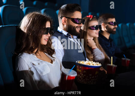 We always go together to the movies. Shot of a group of friends smiling cheerfully while watching a 3D movie together - Stock Photo