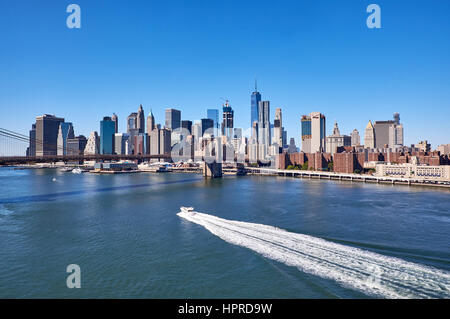NEW YORK CITY - SEPTEMBER 25: View over East River with a motorboat making a white wake trail in front of the Manhattan - Stock Photo
